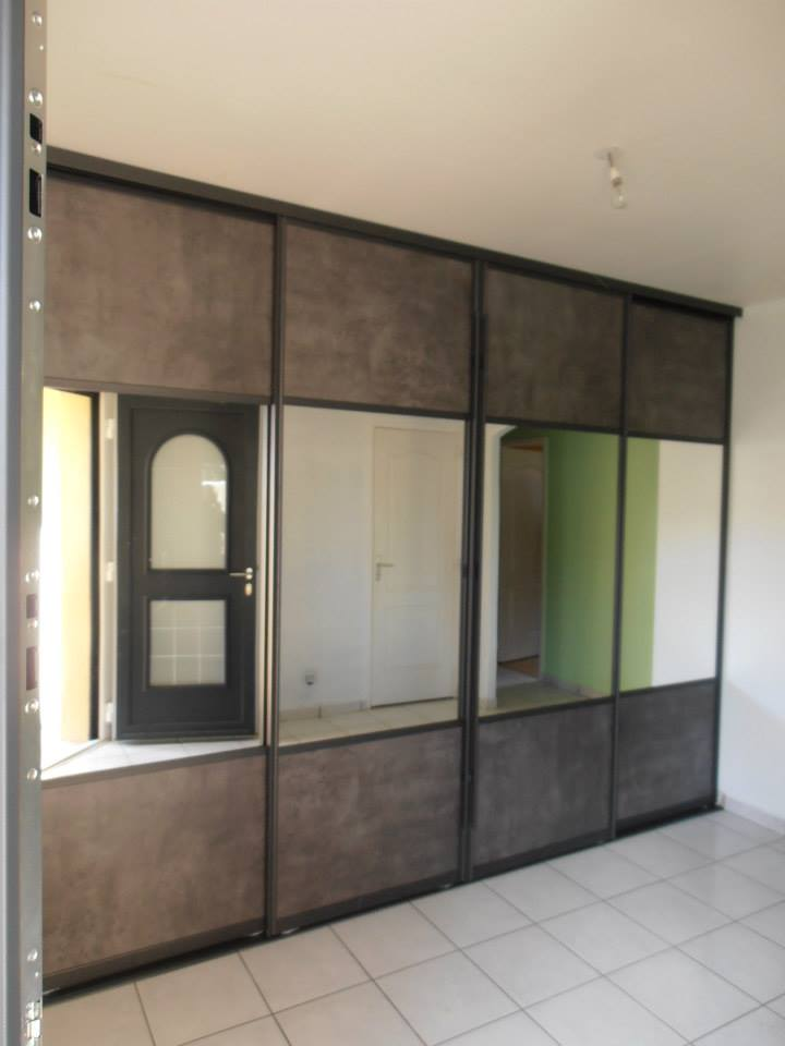 Dressing avec portes de placard coulissantes effet bois et miroir par Loire Agencement