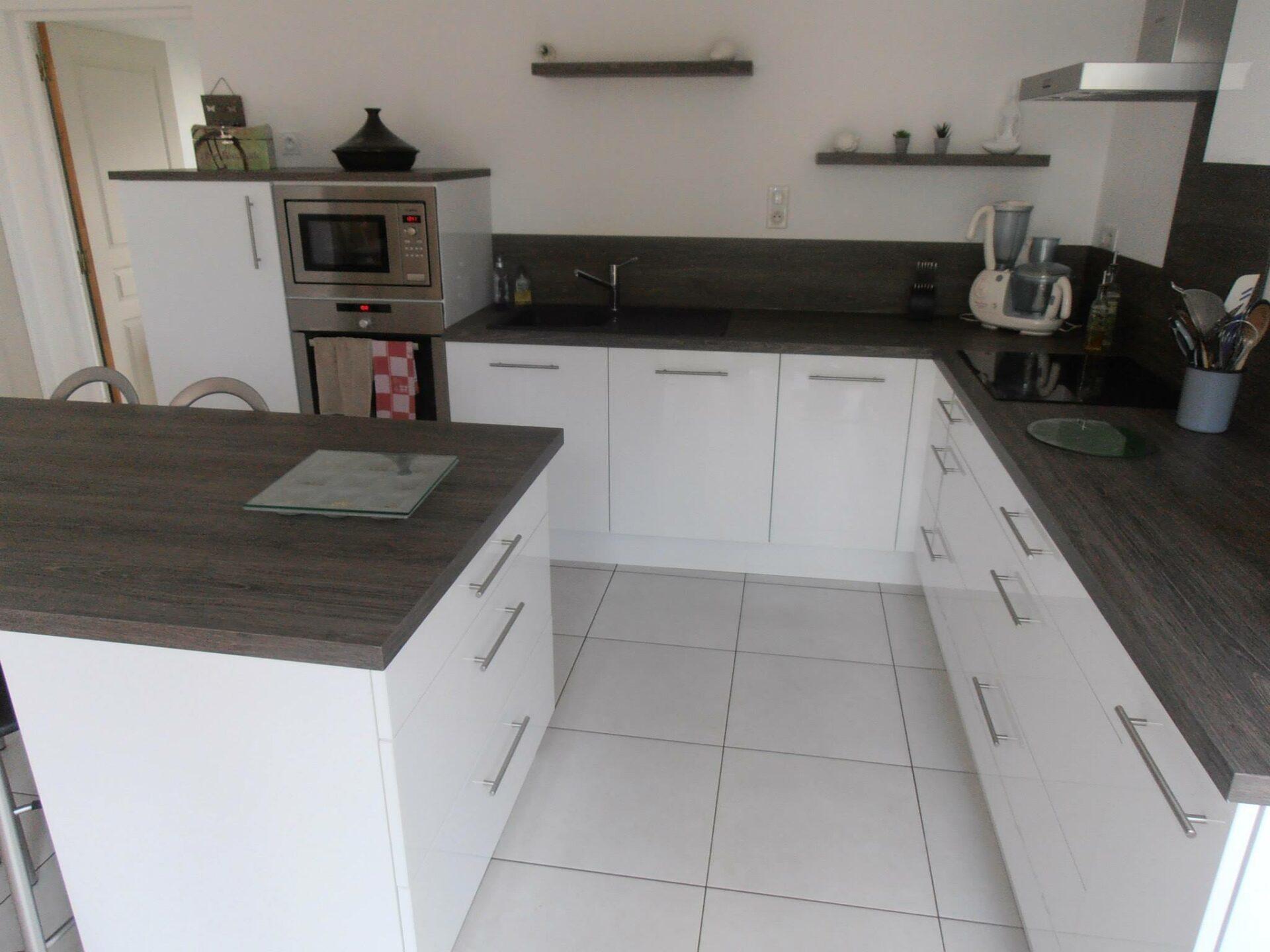 Meubles de cuisine aménagée en bois blanc laqué et plan de travail gris par Loire Agencement à Liré